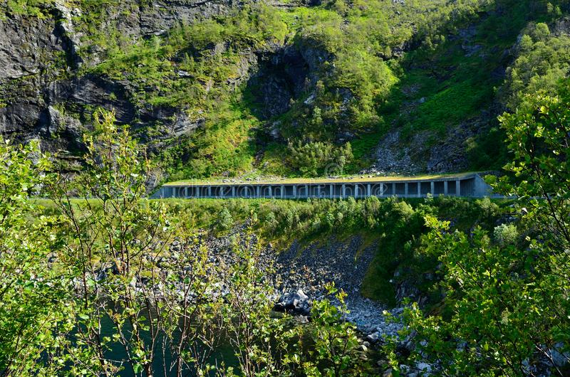 Halb offener Tunnel, der vor Steinschlägen mit Küste darunterliegend sich schützt lizenzfreies stockbild