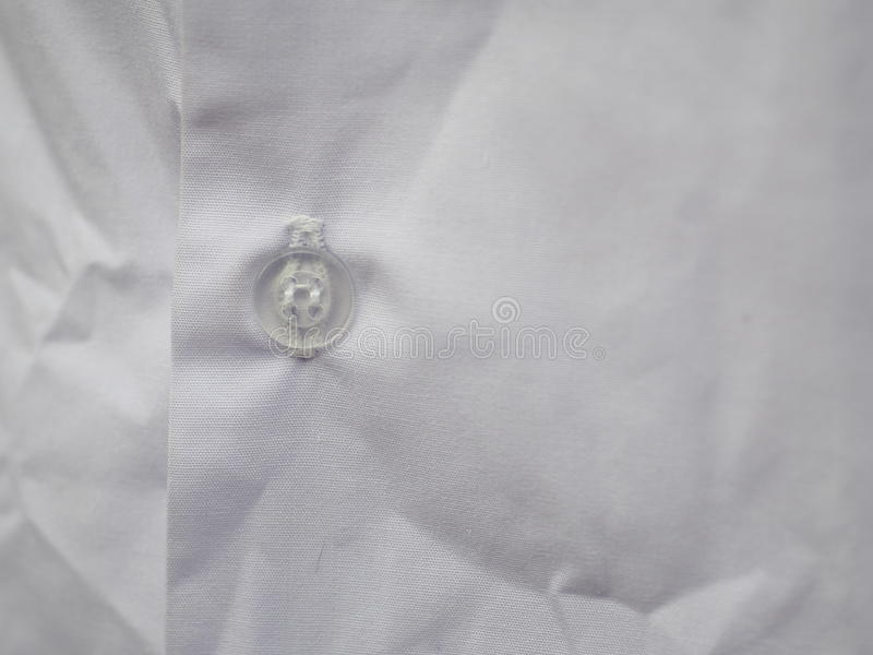 Halb transparenter Plastikknopf auf weißem Baumwollhemd stockbilder