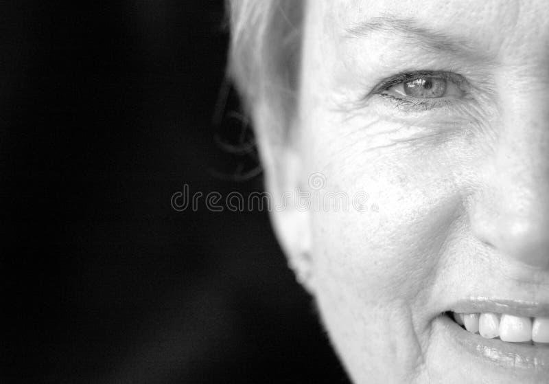 Halbe Gesichtsälterfrau lizenzfreies stockfoto