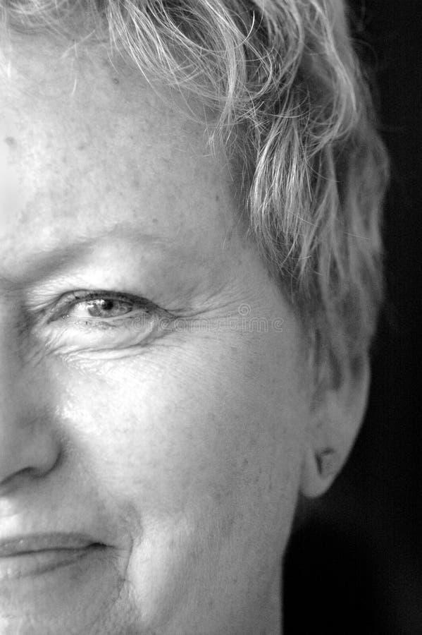 Halbe Gesichtsälterfrau lizenzfreie stockfotos