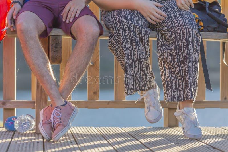Halbe Körperansicht, Unterseite, junges Paar, das auf einer Holzbank, er eine Zigarette rauchend sitzt stockbilder