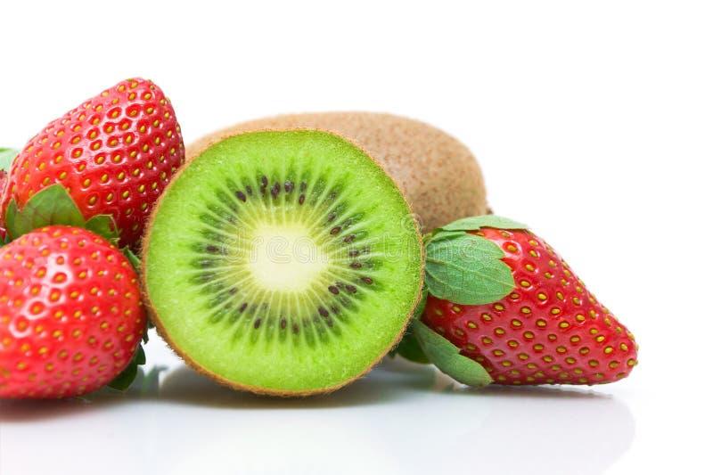 Halbe Kiwi und Erdbeernahaufnahme auf weißem Hintergrund lizenzfreies stockbild