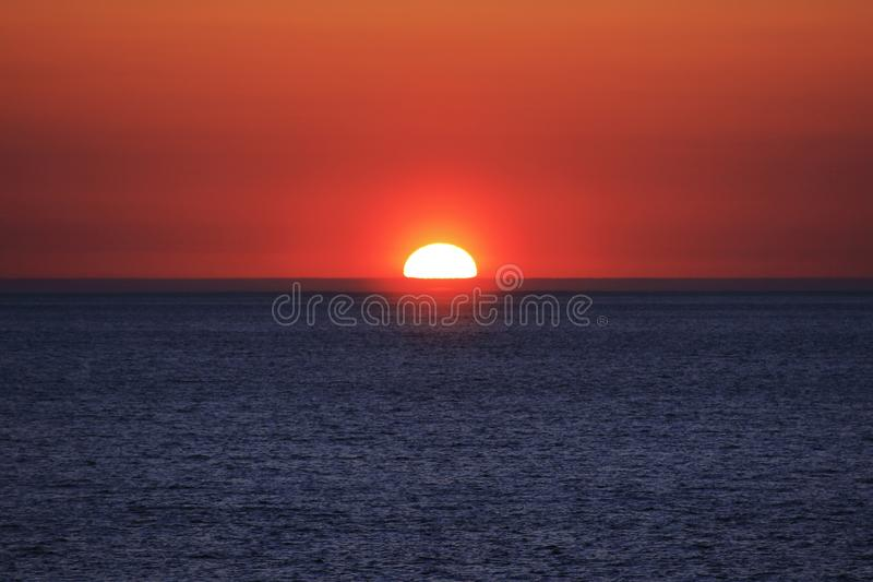 Halbe Sonne in einem schönen Sonnenuntergang lizenzfreies stockbild