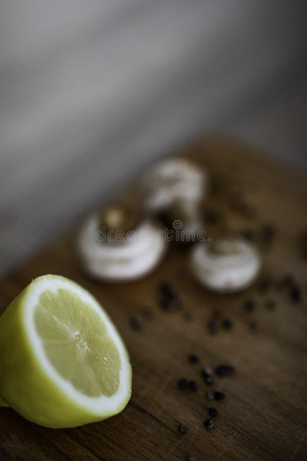 Halbe Zitrone auf einem hölzernen Schneidebrett mit Pilzen und schwarzem Pfeffer stockfoto