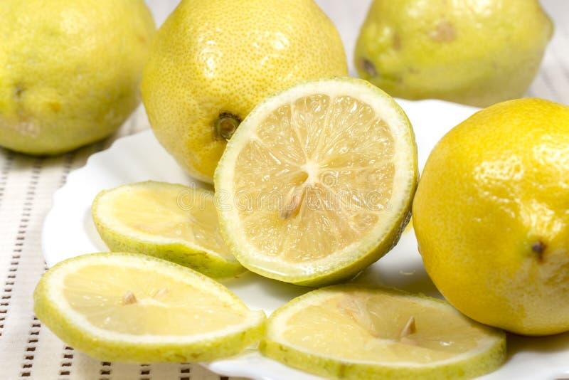 Halbe Zitrone und Scheiben neben einigen vollen Zitronen stockfotografie