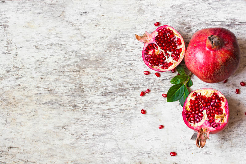 Halber Granatapfel und reifer Granatapfel tragen auf weißem hölzernem rustikalem Hintergrund Früchte stockfotografie