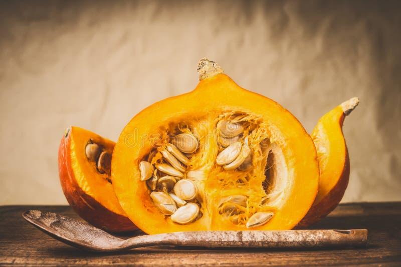 Halber Kürbis mit Samen und hölzernem kochendem Löffel am natürlichen beige Hintergrund, Vorderansicht Saisonlebensmittel des ges lizenzfreie stockfotos
