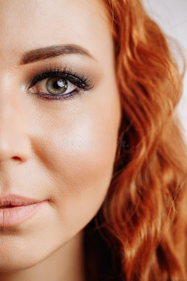 Halbes Gesicht der jungen schönen Rothaarigefrau stockfoto