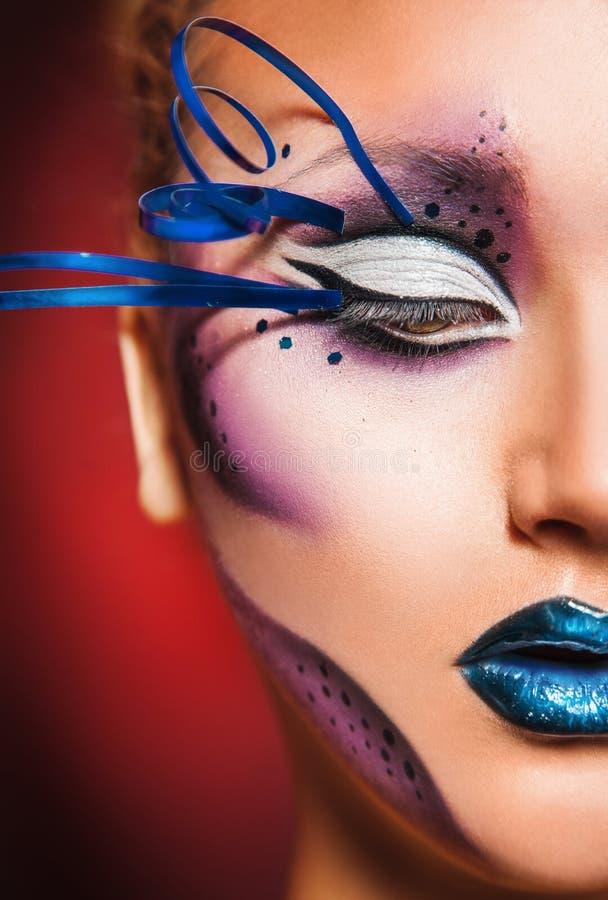 Halbes Gesicht der Schönheitsfrau mit kreativem bilden im Studio auf Rot stockfoto