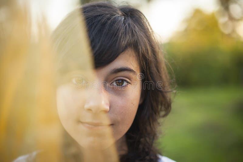 Halbes Gesicht des Porträts des jungen Mädchens versteckt hinter einem Schleier stockbilder