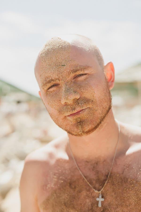 Halbes Gesicht eines gutaussehenden Mannes bedeckt mit Sand stockbild