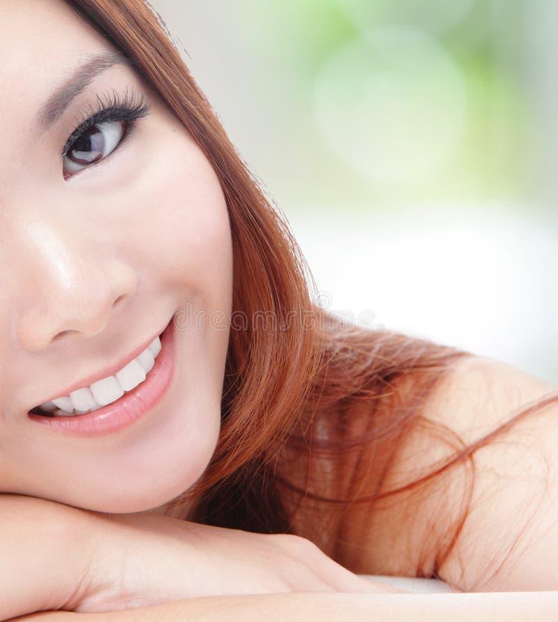 Halbes Lächeln der jungen Frau des Gesichtes mit den Gesundheitszähnen lizenzfreies stockfoto