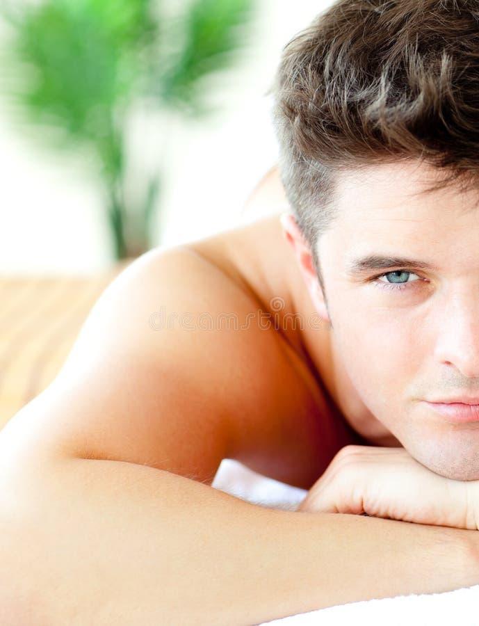 Halbes Portrait eines stattlichen Mannes, der auf einer Massage liegt lizenzfreies stockfoto