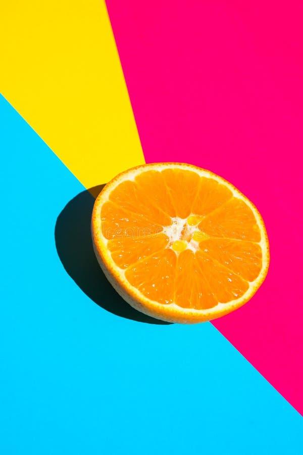 Halbierte reife saftige Orange auf klarem pinkfarbenem blauem gelbem Hintergrund Helles raues Sonnenlicht-tiefer Schatten Vibrier stockbilder
