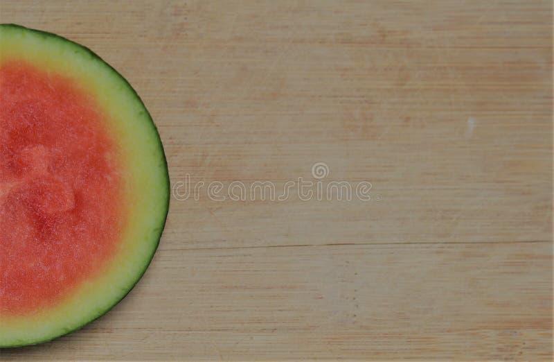 halbkreisförmig geschliffene Wassermelone, am Rand eines abgenutzten Bambusschneidbrettes lizenzfreies stockbild