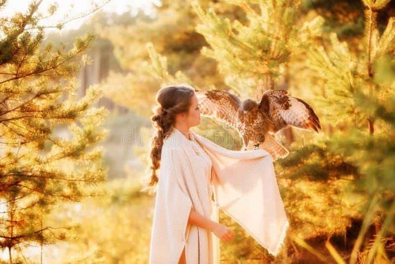 Halcón con las alas separadas que se sientan en el brazo de una muchacha hermosa fotografía de archivo