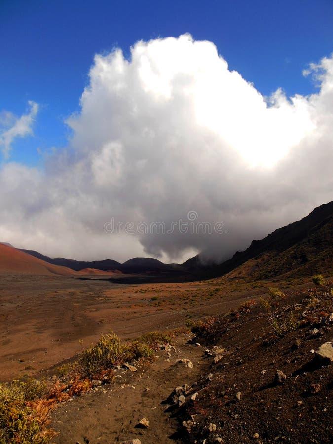 Haleakala Crater. A massive misty cloud rises up from the ocean over the crater rim of Haleakala. The barren landscape located in Haleakala National Park on Maui stock image