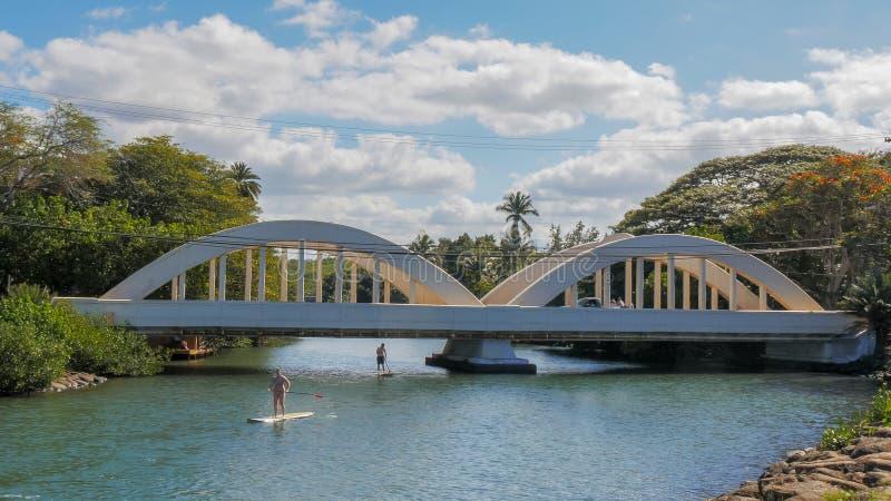 HALEIWA, LOS ESTADOS UNIDOS DE AMÉRICA - 12 DE ENERO DE 2015: los huéspedes de la paleta pasan debajo del puente en haleiwa imagen de archivo libre de regalías