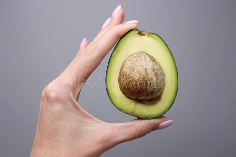 Half of avocado in human hand on gray background stock photos