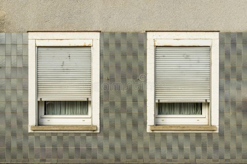 Half betegelde voorgevel, gepleisterd over vensters met half-closed blinden en vensterbank waarschijnlijk van de jaren '60 stock fotografie