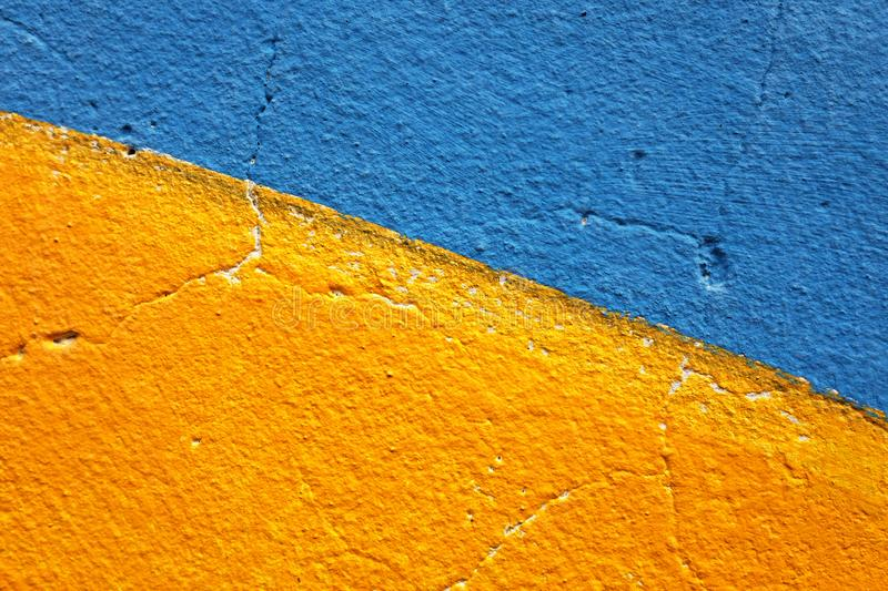 Half of blue and half of yellow painted grunge wall for backgroud royalty free stock photo