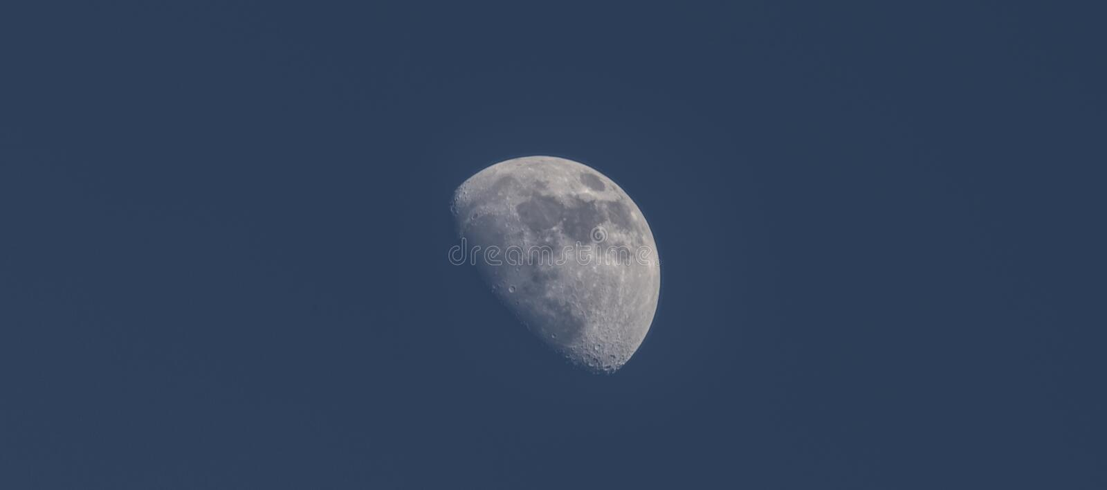 Half blue moon with seas and craters and blue winter sky. Half blue moon with seas and craters and dark blue winter sky stock photography