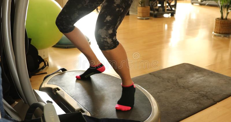 Legs vibration plate. Half body of fit woman warming up in short leggings, training legs on vibration plate step. Modern gym defocused background. Female athlete royalty free stock images