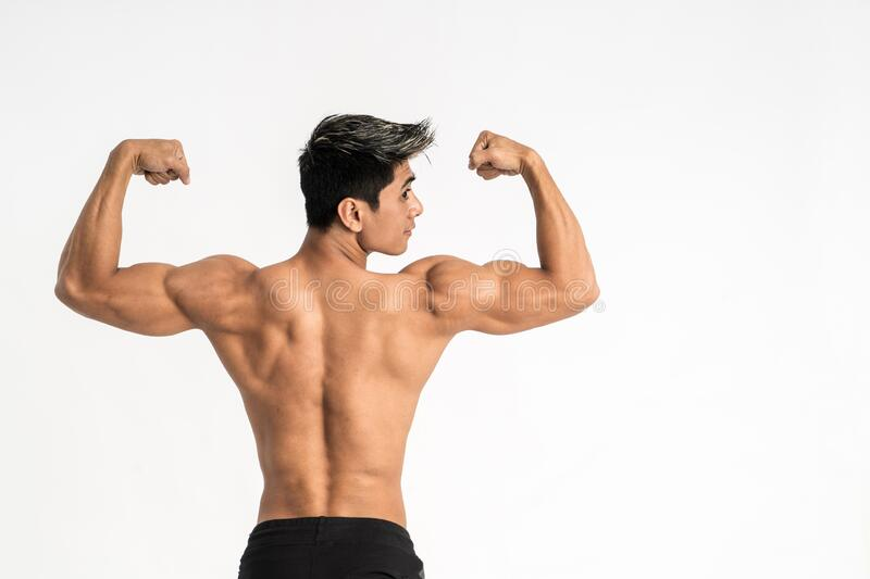 Half body image of young man showing muscular body stand facing back royalty free stock image