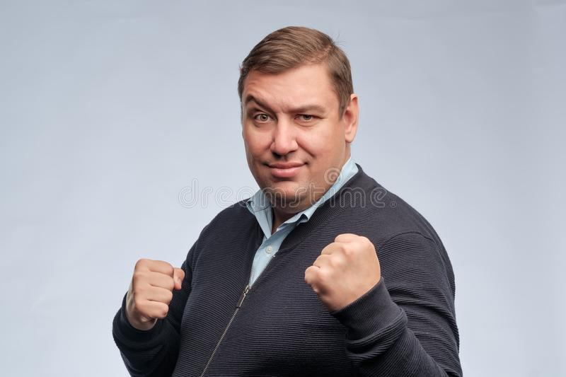 Half body portrait of confident middle aged man with folded arms looking at camera. He is ready to fight royalty free stock photo