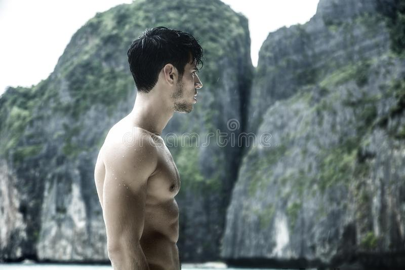 Young man standing on edge of the ocean stock image