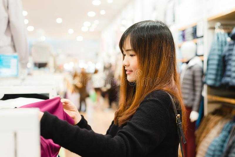 Half body shot of a happy asian young woman with shoulder bag looking at clothes hanging on the rail inside the clothing shop. stock images