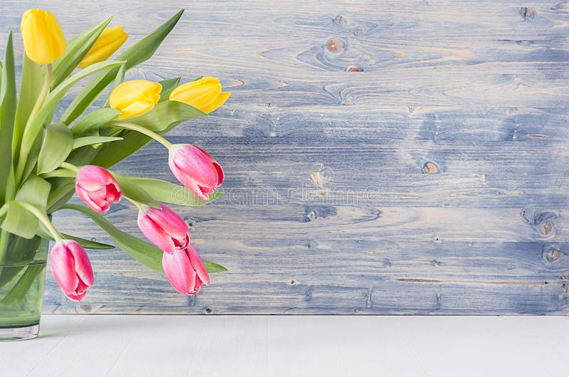 Half bouquet red and yellow tulips in green glass vase on blue shabby wooden background with copy space. Spring easter home decor. stock photos