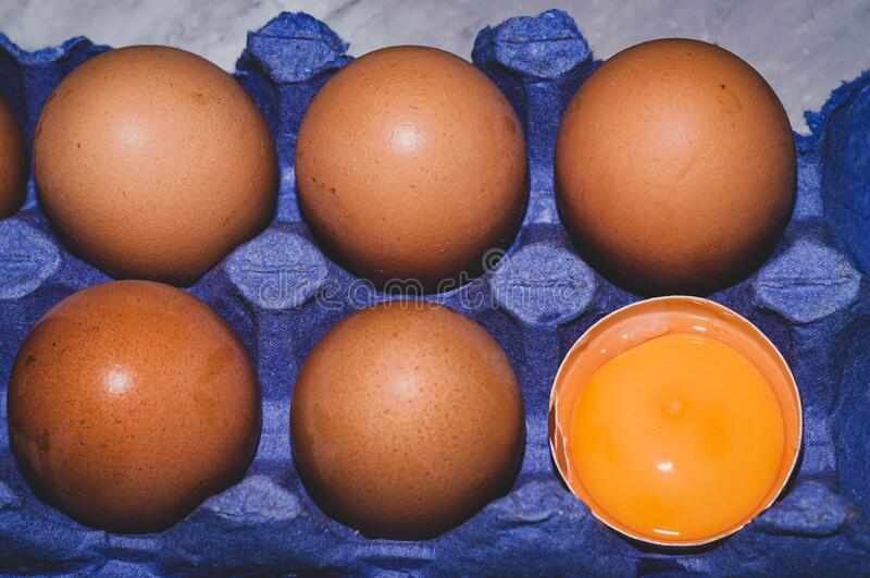 Half broken fresh chicken egg with orange yolk in shell near among other eggs in purple paper royalty free stock images