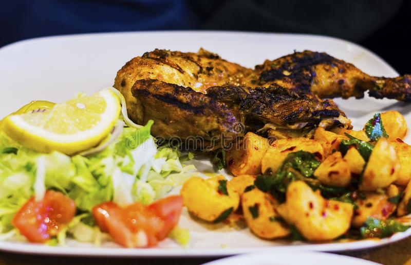 Half Chargrilled Chicken with Salad and Spicy Potatoes. Authentic Lebanese Dish royalty free stock image