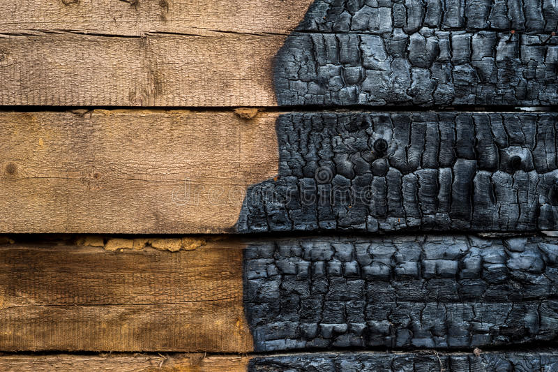 Half charred wood. En wall of the house, contrast stock photo