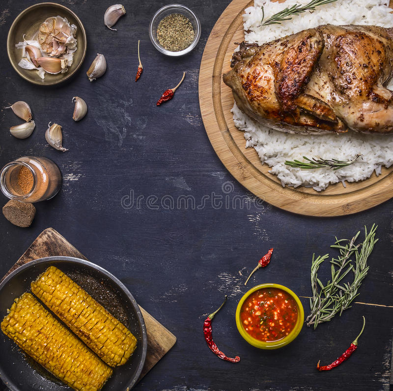Half chicken with rice on a cutting board with spices, corn and herbs, place for text,frame wooden rustic background top view stock images