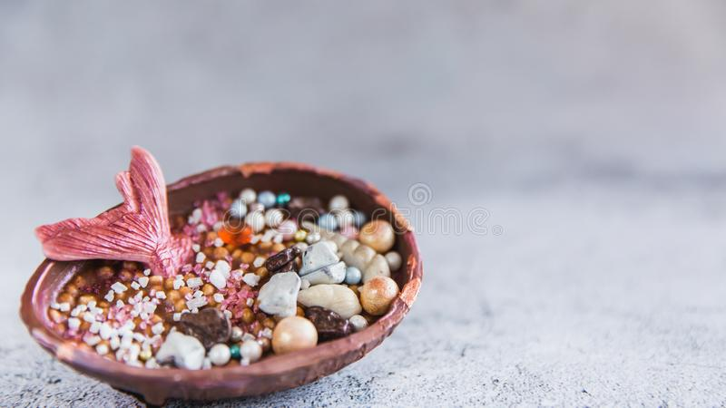 Half a chocolate egg filled with popped rice. The egg is decorated with precious stones and a mermaids tail stock photos