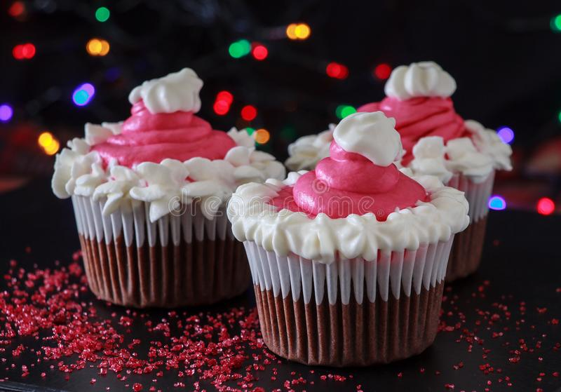 Half of Christmas homemade chocolate cupcake with pink cream cheese frosting. Blur light and dark background. Three Christmas homemade chocolate cupcake with stock images