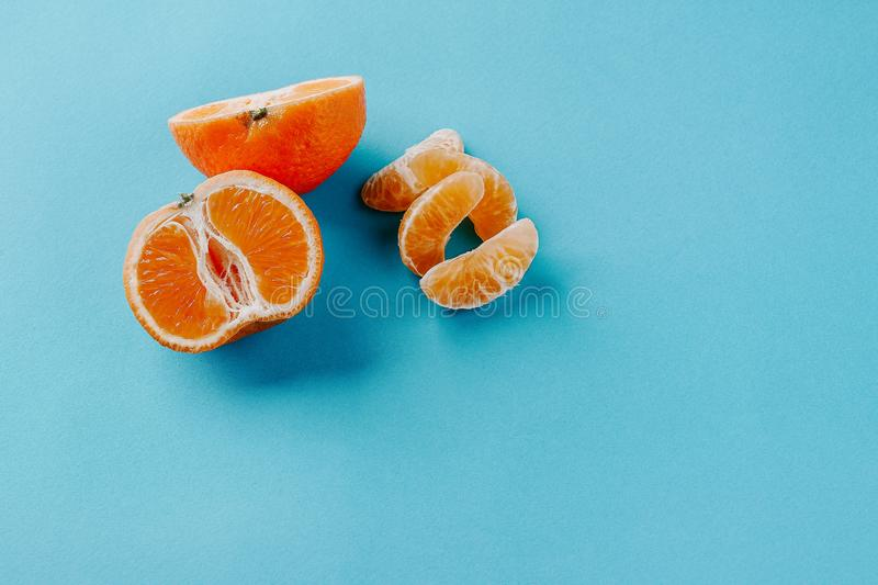 Half the clementines and a few slices on a blue background with copy space royalty free stock photography