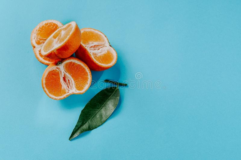 Half the clementines and a leaf on a blue background with copy space royalty free stock photos