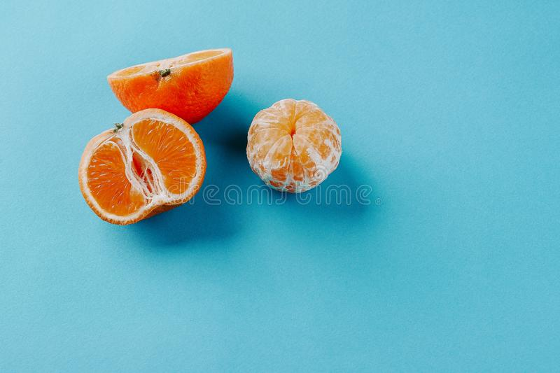 Half of clementines and one peeled on a blue background with copy space royalty free stock photos