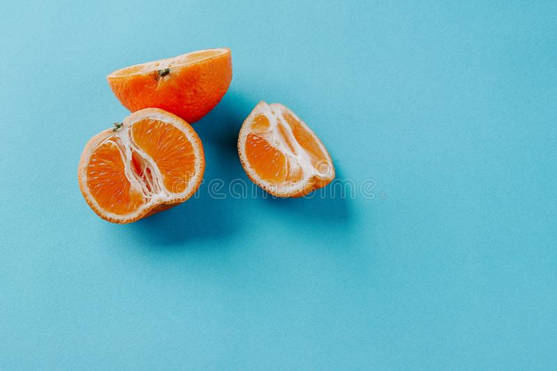 Half the clementines and a quarter on a blue background with copy space stock photos