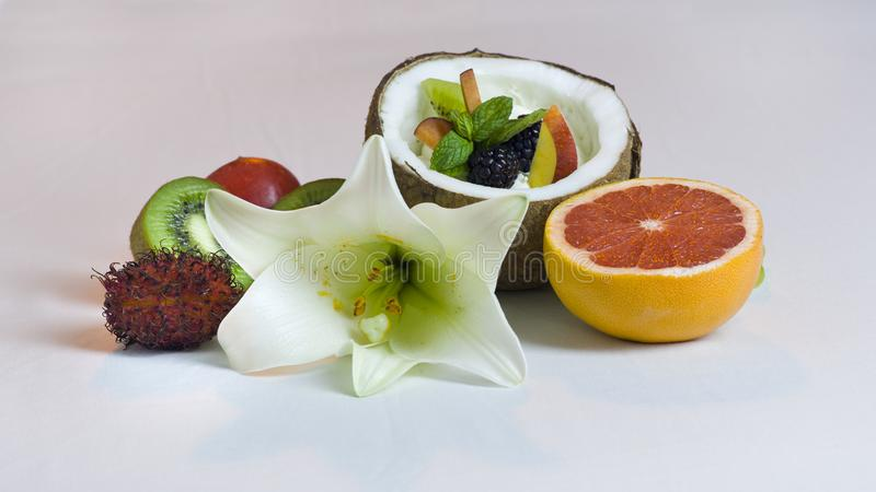 Half Coconut with Cream and Fresh Fruits Salad Still Life. Composition stock photos