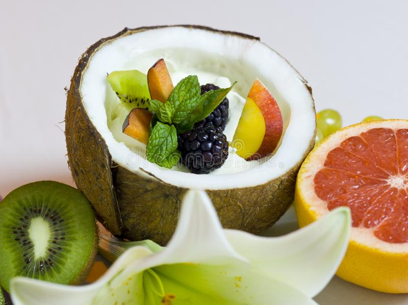 Half Coconut with Cream and Fresh Fruits Salad. Still Life Composition stock photography