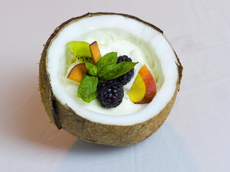 Half Coconut with Cream and Fresh Fruits Salad Still Life. Composition royalty free stock image
