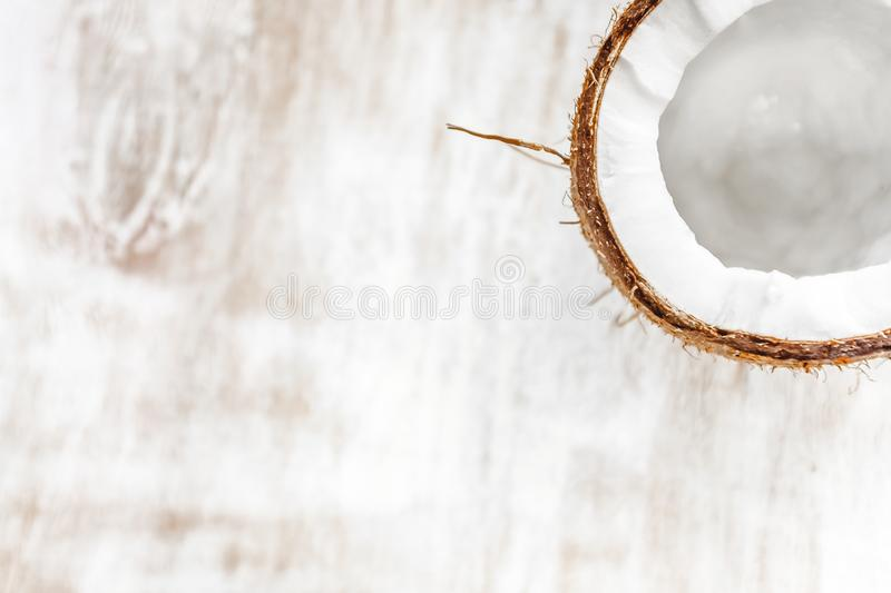 half coconut on a light white wooden background, closeup. Top view royalty free stock photography
