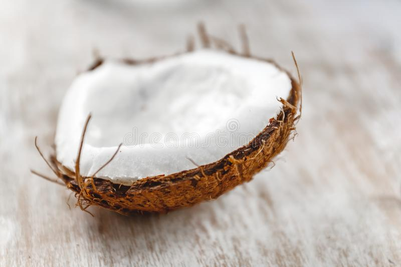 Half coconut on a light white wooden background, closeup. Top view stock photography