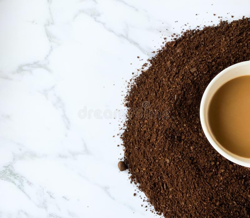 Half of coffee`s cup on roasted and ground coffee beans isolated on white marble background stock image