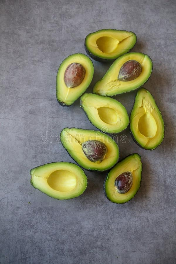 Half cut ripe avocados with seed on dark grey background, top view flt lay stock image