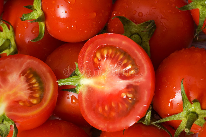 Half cut and whole tomatos stock images